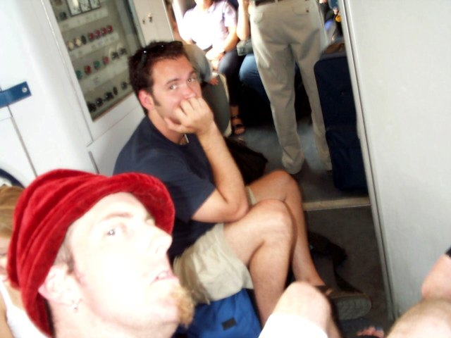 Sitting on Our Backpacks in front of the WC on the Train after 2½ Hours of Sleep